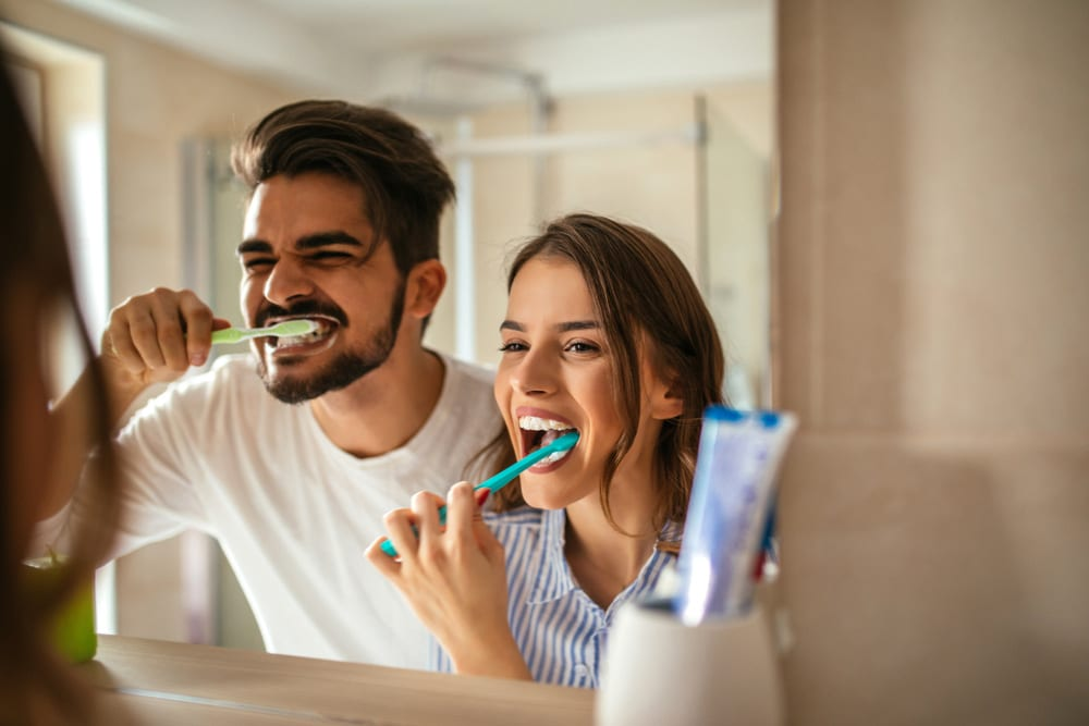 A couple brushes their teeth together following West Richland Family Dental's top 10 ways to take care of your teeth list