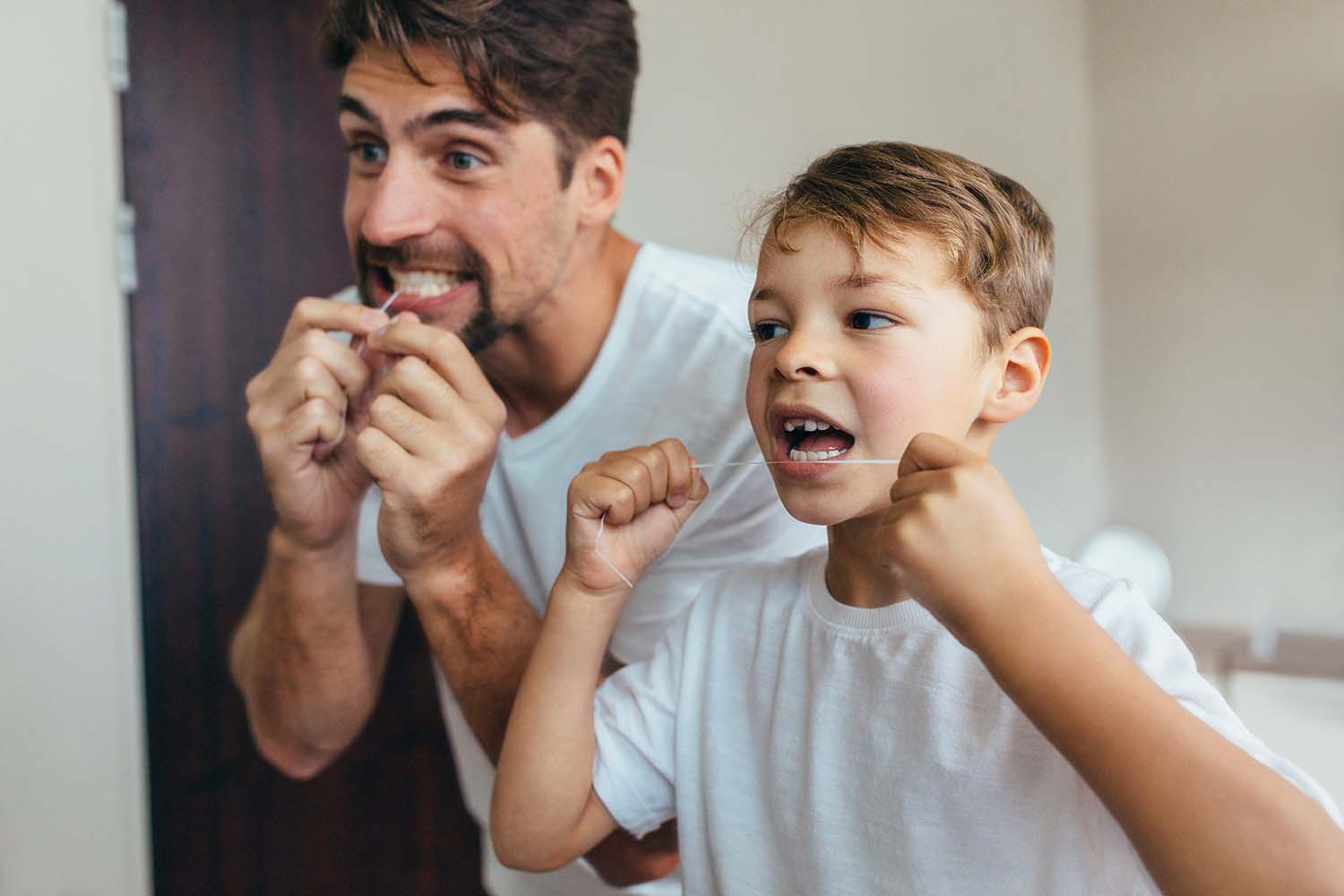 A father and son, patients at West Richland Family dental, floss together during their daily home oral care routine.